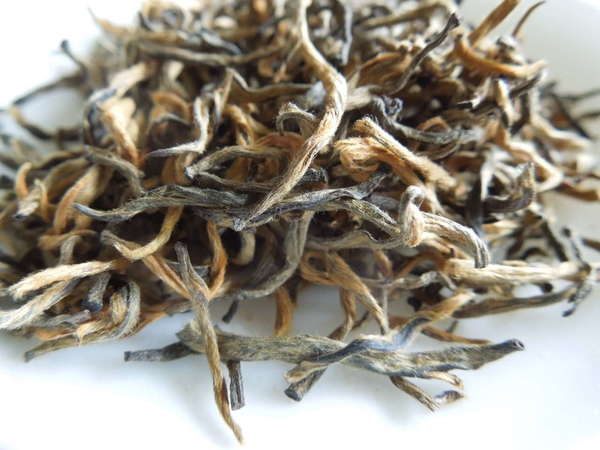 Loose-leaf Tea with golden-orange and gray-black twisted, hairy leaves