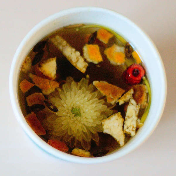 Flowers and citrus peel steeping as a dark brown herbal tea in a white cup