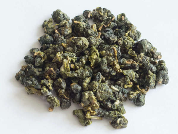 Tightly-rolled oolong tea leaves, bright green with golden and dark green accents, on white background