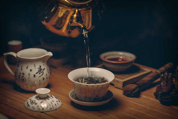 A metal tea kettle pouring hot water into a gaiwan with loose-leaf tea, other teaware surrounding on table