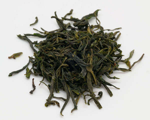 Loose-leaf green tea with long, wiry, dark green leaves with golden hints, on white background