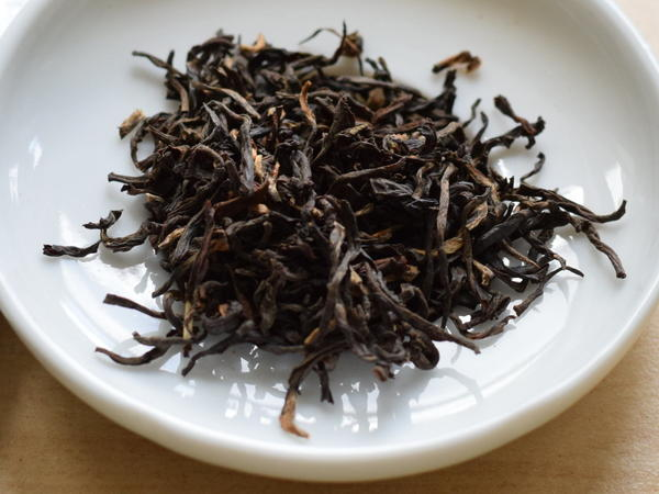 Wiry, crinkly black tea leaves with golden tips, in a white dish