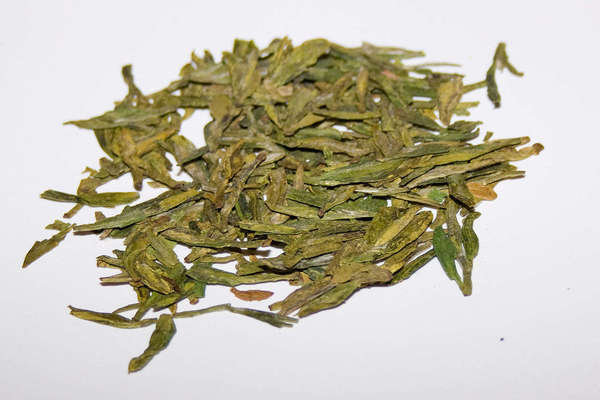 Loose-leaf green tea with long, flat, yellow-green leaves on a white background