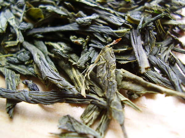 Loose-leaf green tea with large, intact, somewhat wrinkly leaves, dark gray-green with yellow-green hues