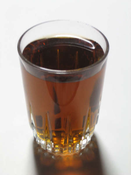 Glass filled with dark brown transparent drink