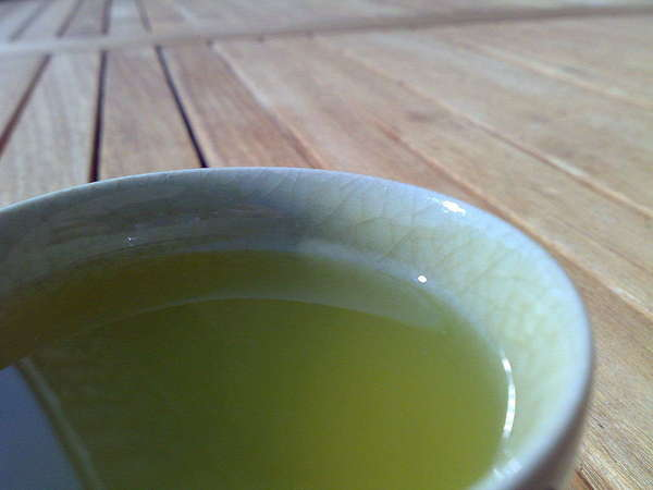Bright green tea in ceramic cup, on wooded table with slats