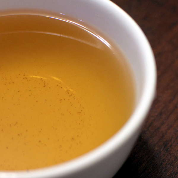 Golden-yellow tea in white teacup on dark wooden background