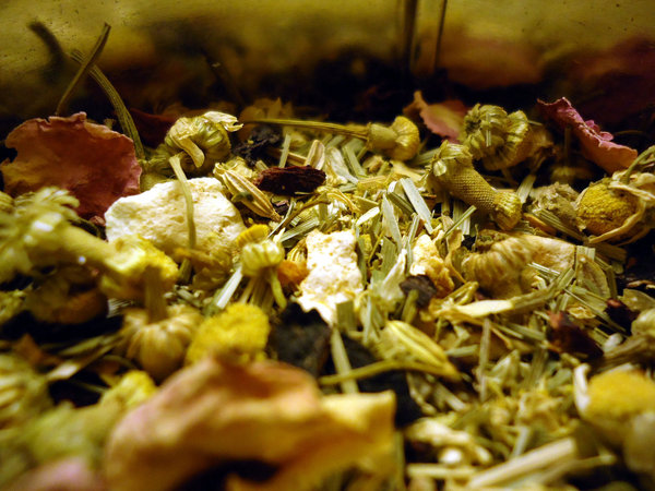 Mix of various herbs, with chamomile blossoms, dried lemongrass, and flower petals visible