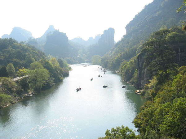 Broad river with very steep slopes, winding through craggy mountains with dense forest cover