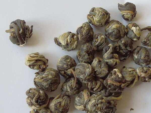 Small round balls made up of rolled-up tea leaves, silvery-golden to gray-green in color