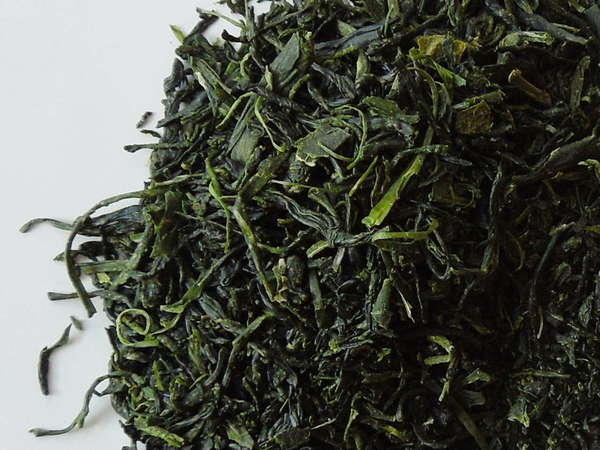 Loose-leaf green tea with vibrant dark green color and wiry, slightly curved leaves
