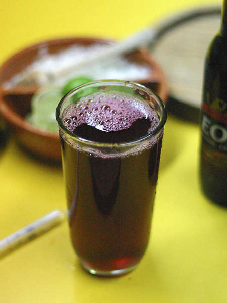 Glass filled with dark purple-red drink, a bowl in the background and a bottle on the right, background blurred, on a yellow surface